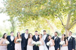 wedding-party-smiling-outdoors-pink-dresses-blue-suits-bouquets-trees-california-wedding
