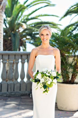 bride-in-strapless-ines-di-santo-wedding-dress-bouquet-of-white-flowers-greenery-palm-trees