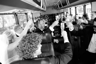 black-and-white-photo-of-bridal-party-champagne-toast-in-the-shuttle