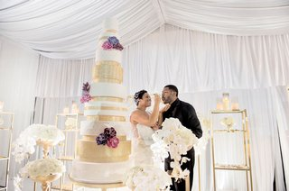 bride-feeding-groom-cake-tall-white-and-gold-sparkle-wedding-cake-with-flowers-on-tiers-white-orchid