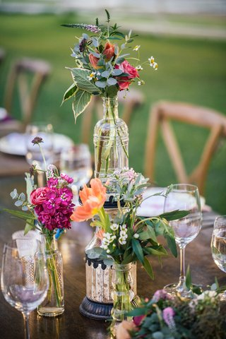 outdoor-bohemian-wedding-reception-table-with-decorative-vases-bottles-with-bundles-of-pink-flowers