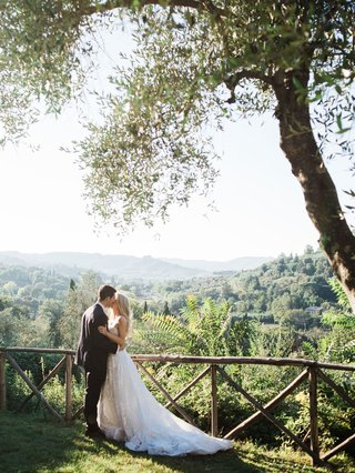 bride-and-groom-portrait-sunlight-italy-countryside-view-of-landscape-olive-trees-strapless-wedding