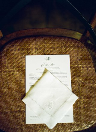 ceremony-program-and-handkerchief-on-guest-seat-at-wedding-ceremony-with-custom-monogram