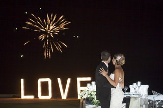 bride-and-groom-watching-fireworks-show-over-ocean-at-destination-wedding-in-mexico