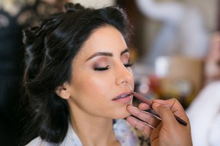 bride-getting-makeup-done-on-wedding-day-hair-pulled-back-natural-makeup-pink-lip-and-eyeshadow