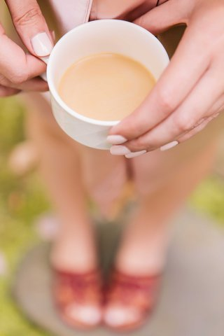 bridesmaid-with-cream-painted-nails-displays-a-cup-of-coffee-while-getting-ready