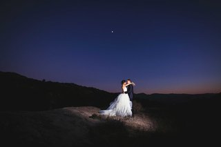 newlywed-bride-and-groom-embracing-during-night-reception-in-outdoor-space-southern-california