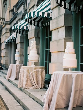 wedding-cakes-displayed-on-small-tables-with-linens-at-wedding-reception-outdoors-by-pool-dc
