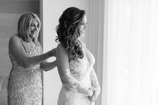 black-and-white-photo-of-mother-of-bride-helping-daughter-into-ines-di-santo-wedding-dress-bridal