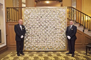 attendants-by-wall-of-escort-card-display-on-florals-with-gold-hatching