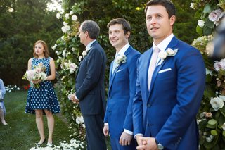 groom-in-blue-suit-next-to-officiant-and-maid-of-honor-in-blue-dress