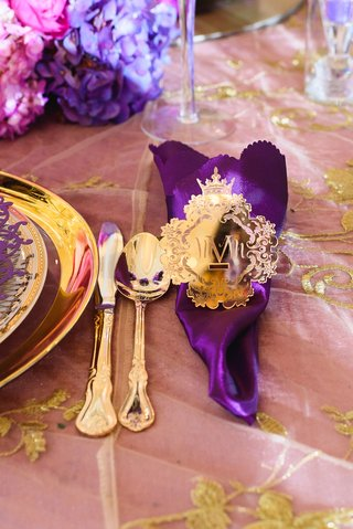 opulent-shiny-gold-napkin-ring-with-monogram-around-royal-purple-napkin-and-gold-flatware