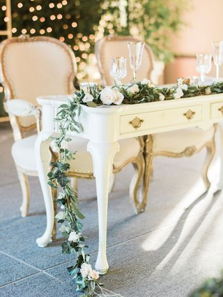 white-antique-desk-sweetheart-table-throne-chairs-garland-greenery-white-flowers