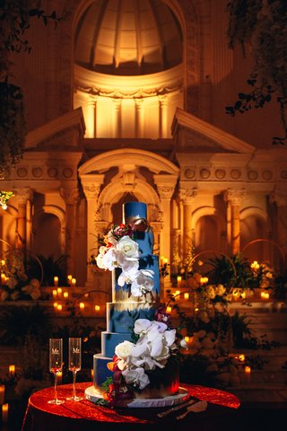 six-tier-blue-cake-with-gold-foil-and-white-orchids-and-roses