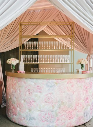 wedding reception cocktail hour pink flower print bar on quilted tufted bar gold details