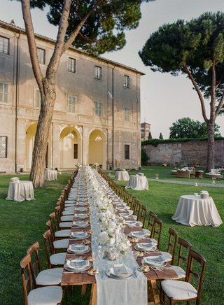 long-wooden-table-on-lawn-outside-historic-italian-building
