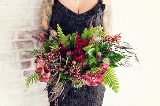 bride-in-a-black-gown-with-appliques-beading-carries-bouquet-of-greenery-red-roses-orchids