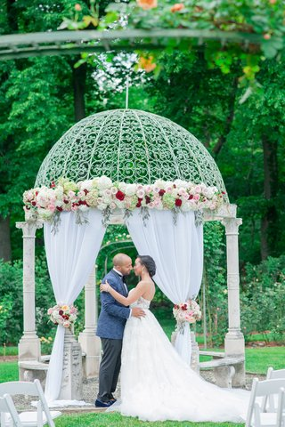 bride-and-groom-at-gazebo-as-altar-with-blush-and-marsala-roses-drapery