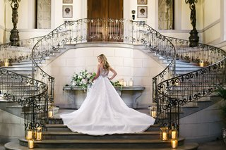 back-of-angel-sanchez-wedding-dress-in-grand-stairway-at-oheka-castle