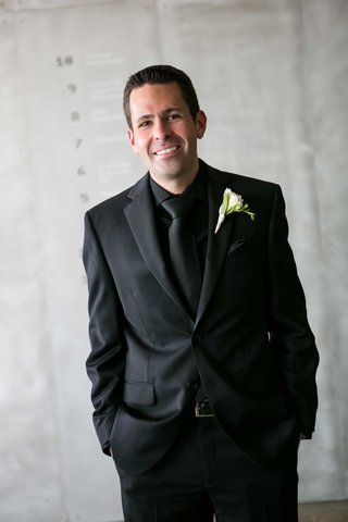 a-groom-in-an-all-black-tuxedo-ensemble-with-simple-white-and-green-boutonniere