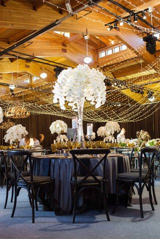 aspen-colorado-wedding-reception-in-wood-barn-with-dark-linens-chairs-and-tall-white-orchid-flowers