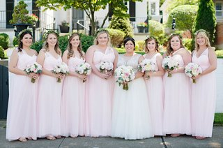bride-with-seven-bridesmaids-pale-pink-gowns-mismatched-necklines-matching-bouquets-greenery-crowns
