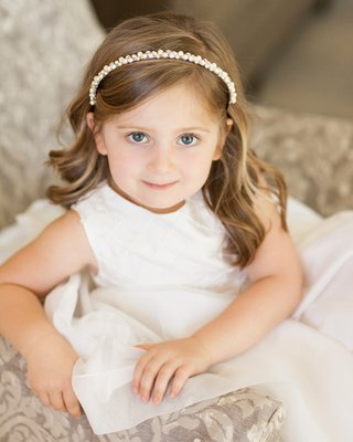 flower-girl-in-white-dress-on-chair-with-pearl-headband
