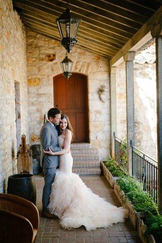 bride-in-blush-ruffled-mermaid-dress-groom-in-grey-suit-hug-during-first-look