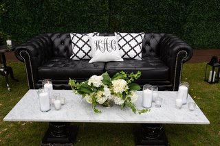 wedding reception outdoor lounge area black tufted chesterfield sofa marble coffee table greenery