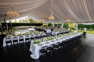 wedding reception white tent hedge wall black chairs white linens ivory greenery centerpieces