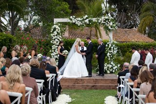 wedding ceremony grass lawn dark wood stain stage white arch flowers greenery