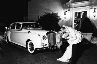black-and-white-photo-of-bride-and-groom-kissing-in-front-of-rolls-royce-classic-car-wedding