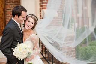 bride-and-groom-smile-in-front-of-brick-building
