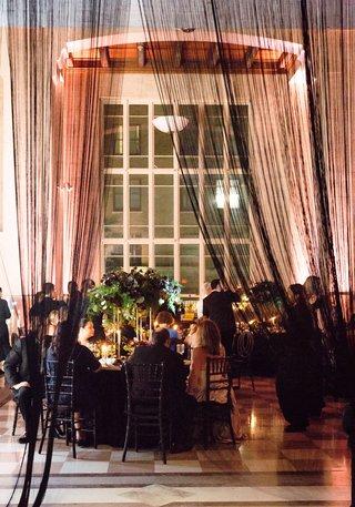 wedding-reception-ballroom-black-sheer-drapery-at-entrance-to-reception-dark-flowers-greenery-candle