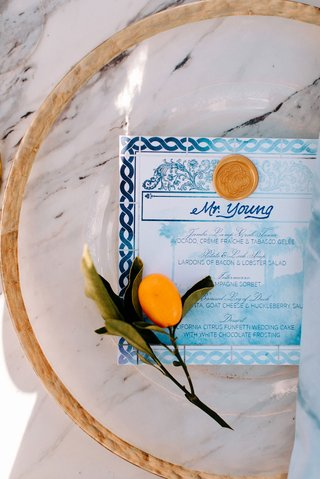 wedding reception fresh fruit kumquat on top of gold charger blue white menu with gold wax seal