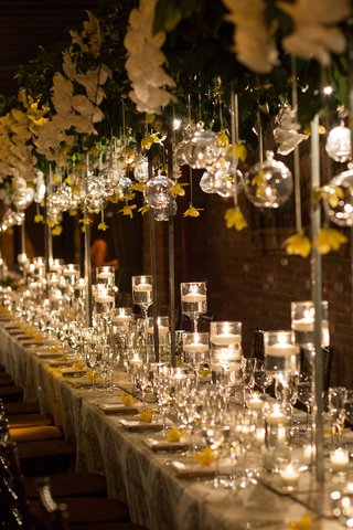 wedding-reception-trellis-centerpiece-with-candles-on-table-yellow-flowers-glass-orbs