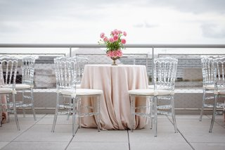 wedding-cocktail-hour-tables-with-light-pink-linens-and-flowers-clear-chairs-white-cushions