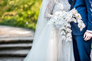 bride-in-lace-wedding-dress-long-sleeves-with-orchid-bouquet-phalaenopsis-orchids-white