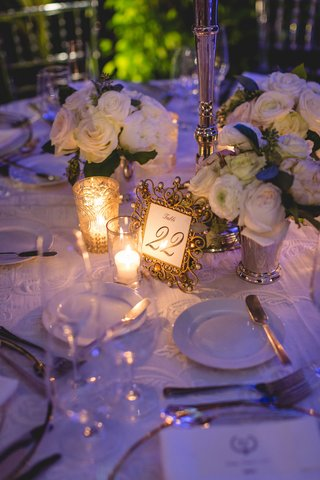 wedding-reception-purple-lighting-white-flowers-gold-ornate-frame-for-number-candles