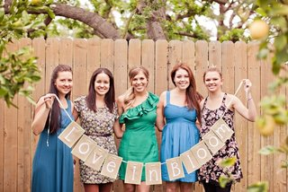 bride-and-bridesmaids-holding-banner-sign-at-bridal-shower