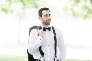 groom-with-stubble-bears-carrying-jacket-over-shoulder-while-wearing-suspenders-and-bowties