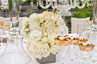 gold-laser-cut-table-number-placed-in-small-white-floral-arrangement-of-roses-hydrangeas-orchids
