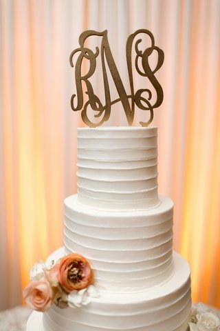 white-textured-wedding-cake-with-orange-flowers-gilded-monogrammed-topper