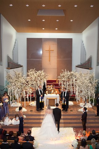 bride-and-groom-standing-at-altar-of-armenian-church-for-wedding-ceremony-with-trees
