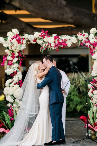 bride-kisses-groom-at-outdoor-ceremony-under-fig-tree-arch-with-white-hydrangeas-pink-bougainvilleas