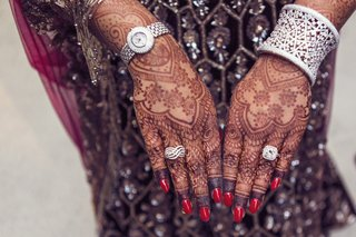 indian-american-bride-with-elaborate-henna-tattoos-on-hands-diamond-engagement-ring-and-right-hand