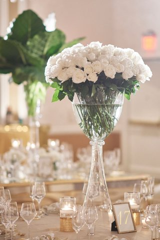 round-table-with-tall-glass-centerpiece-long-stem-white-roses-gold-candles-table-number