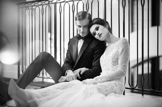 wedding-styled-shoot-model-in-lace-ines-di-santo-gown-leans-head-on-male-model-black-and-white
