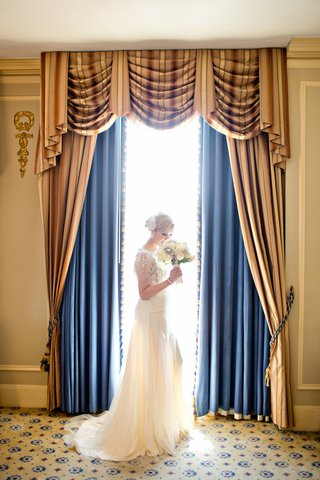 bride-in-a-jenny-packham-dress-holds-white-flower-bouquet-in-front-of-a-window