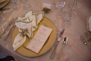 wedding-reception-table-with-golden-charger-menu-gilt-embroidered-napkins-pearl-ties-succulent